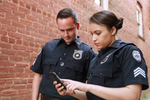 Stock Police Photo showing information lookup by two officers.